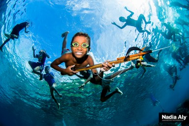 The kids from Tola Bali village love to show off their spearfishing skills to divers from the Damai II. (Nadia Aly)