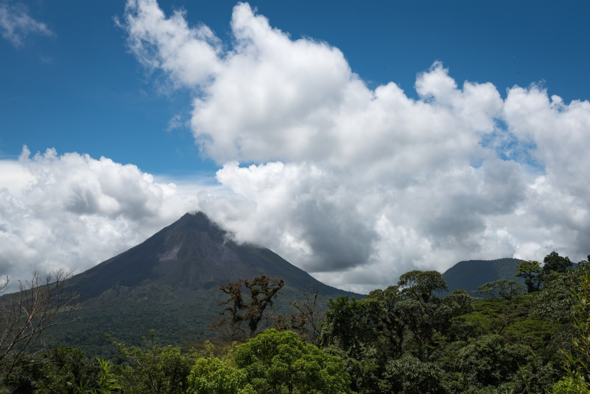 The cone of the commanding Arenal volcano peeks out from a ring of clouds in a rare sighting