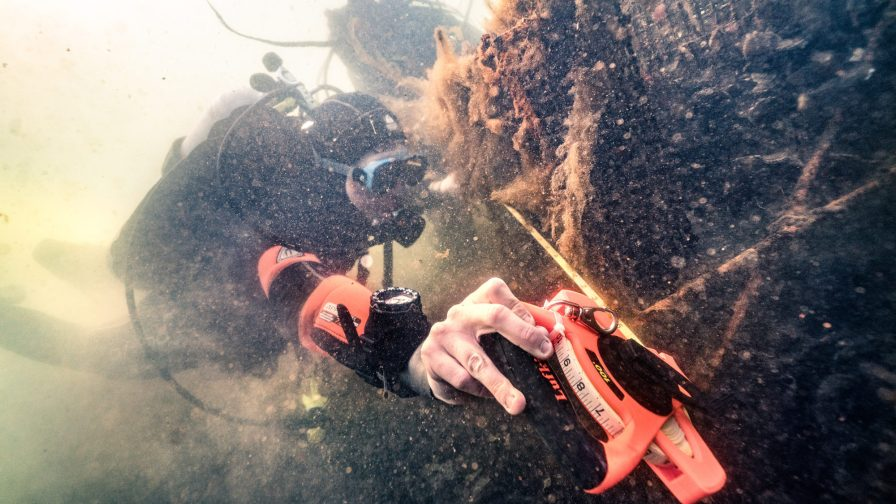 A Professional Diver student measures an artificial oyster reef structure in the murky waters of New York. Photo courtesy of Benjamin Von Wong