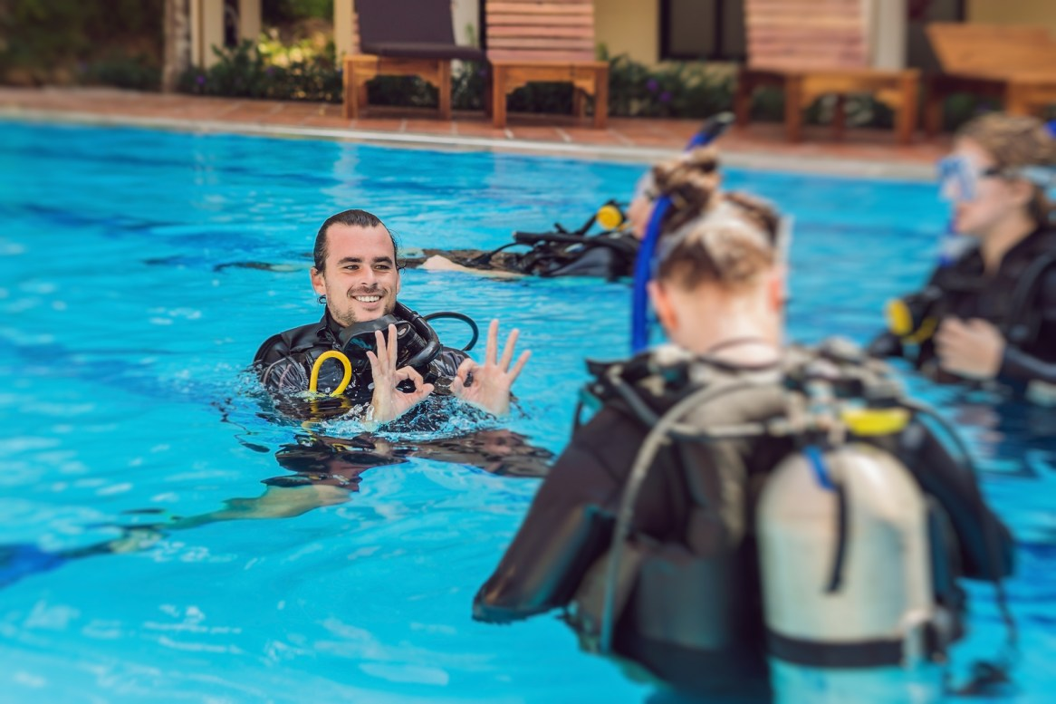 Diving Instructor And Students. Instructor Teaches Students To D