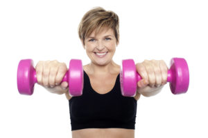 Lady holding pink dumbbells. Arms outstretched. Isolated over white