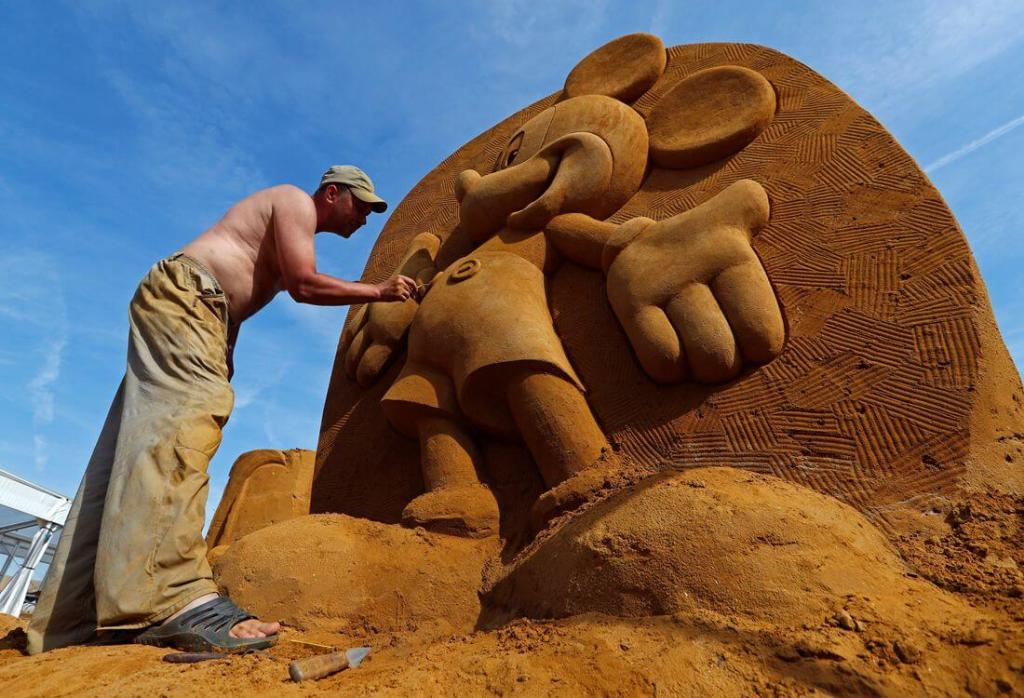 Sand carver Konstantin Kuzyarin works on Mickey Mouse sand sculpture