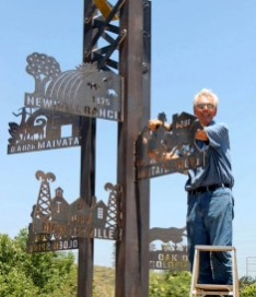 Fabricator Roger Green guides the sculpture onto its base.