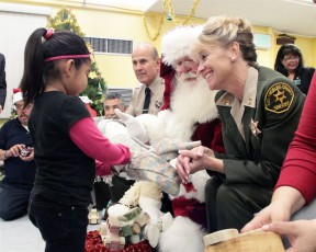 Stuart (foreground) and Sheriff Lee Baca hand out toys collected during the sheriff's 2011 toy drive.