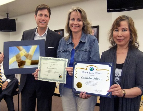 """Cassidy Oliver's mom (center) accepts the award for her artwork, titled """"Colors,"""" from Arts Commissioner John Dow and fellow contest judge Zony Gordon."""