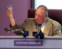 During a June 18 meeting, Winkler offers up a driver's license as evidence of his residency in the district.