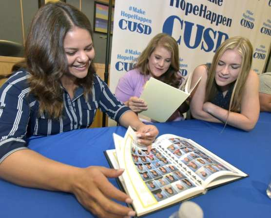 Former students now Castaic Union School District employees, back row from left, Bryahna Alvarez, Miquela Moreno and Samantha Maxey, examine vintage Castaic yearbooks at the Castaic Union School District Board Room on Tuesday. | Photo: Dan Watson/The Signal.