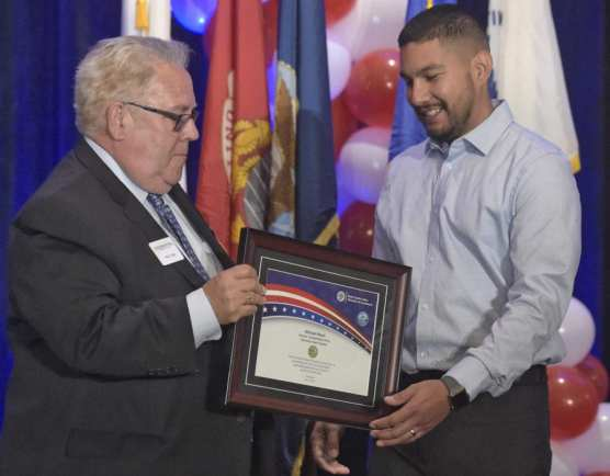 U.S. Army veteran Michael Reyes, right, is presented his plaque for his service in Operation Iraqi Freedom by Hunt Braly during the 9th Annual Patriots Luncheon presented by The Santa Clarita Valley Chamber of Commerce and the City of Santa Clarita at the Hyatt Regency Valencia on Thursday. | Photo: Dan Watson/The Signal.