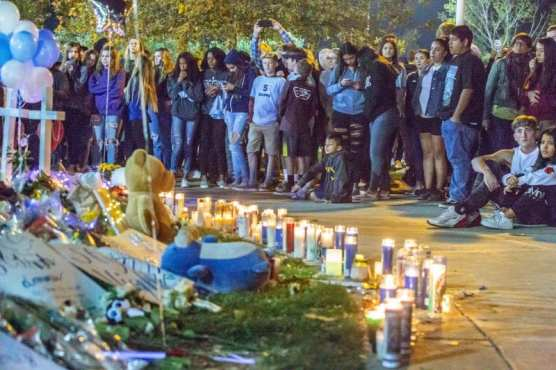 Residents stand around the memorial set up at the Central Park flag pole at the Saugus Strong Vigil Sunday night.   Photo: Cory Rubin / The Signal.