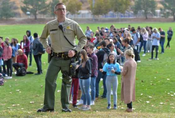 Sheriff's deputies stand guard over hundreds of evacuated Saugus High School students at Central Park in Saugus after a shooting incident at Saugus High School on Thursday, November 15, 2019. | Photo: Dan Watson / The Signal.