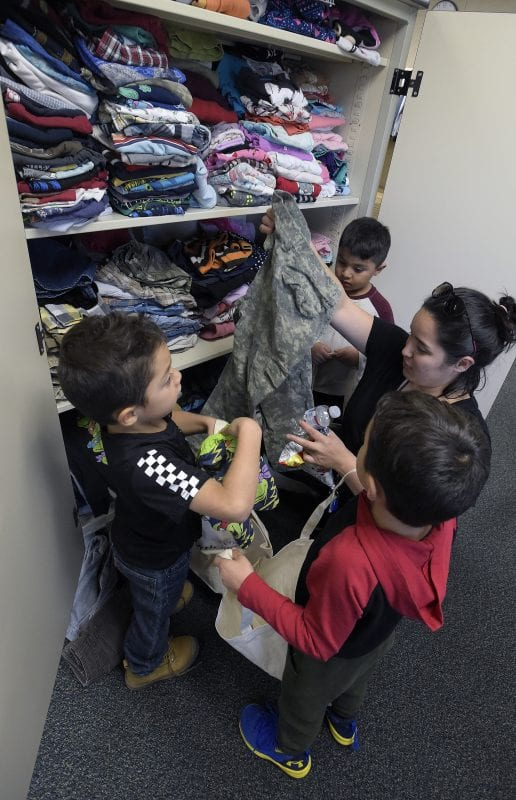 Maria Velez and her three sons from left, Steven,5, Jaden, 4, and Hector Lemus, 5, go through clothes as they are the first family to visit the Wiley Canyon Elementary School Family Resource Center in Newhall on Thursday, November 21, 2019. | Photo: Dan Watson / The Signal.