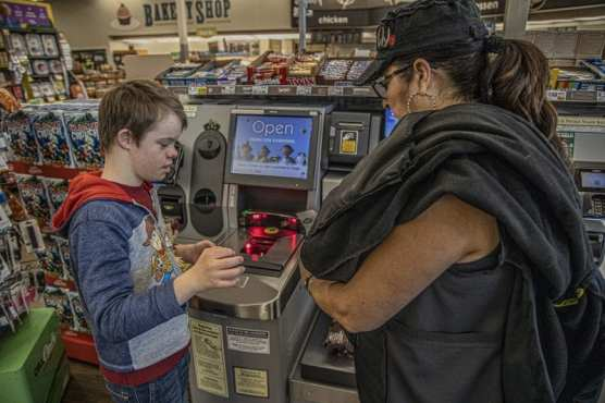 Michael Meyer, a special education student from Pico Canyon Elementary school, learns how to use the self-checkout terminal at Ralphs on a class field trip Thursday morning, December 5, 2019. | Photo: Bobby Block / The Signal.