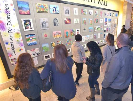 "Attendees examine the more than 60 pieces of artwork displayed as part of the SAFE ""Support Art For Expression"" exhibit created by Rio Norte Junior High seventh and eighth-grade students displayed on the Community Wall in the Westfield Valencia Town Center on Friday, February 7, 2020. 