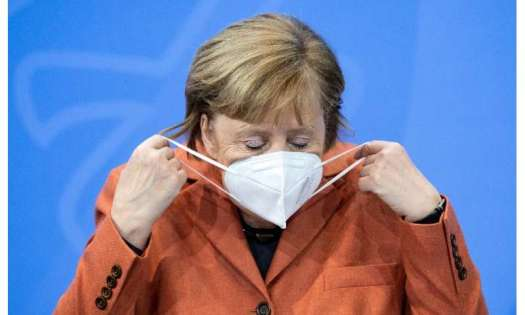 German Chancellor Angela Merkel takes off her face mask before a press conference following talks via video conference with Germ