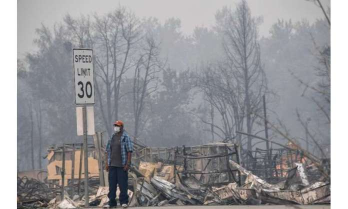 A man stands near some of the destruction caused by the Almeda Fire in Phoenix, Oregon, September 15, 2020