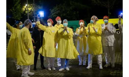 Heathcare workers acknowledge applause outside a hospital in Barcelona
