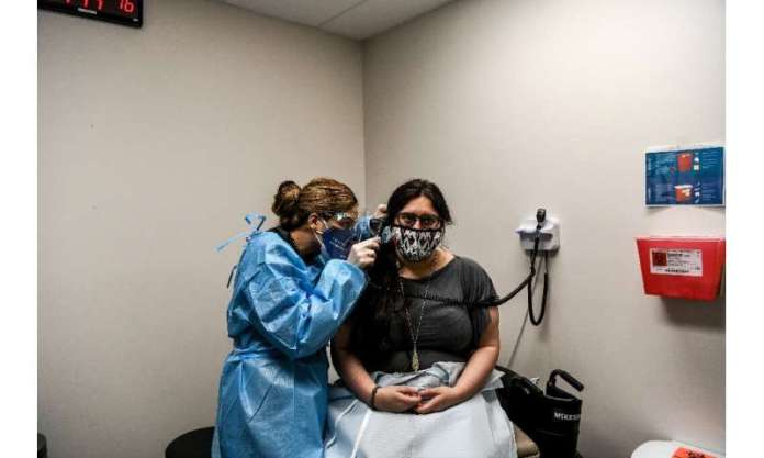 Nelia Sanchez-Crespo (L) examines Heather Lieberman, 28, as she participates in a COVID-19 vaccination study at the Research Cen