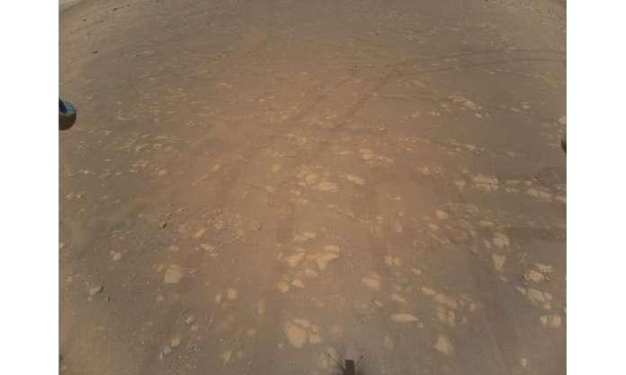 25 अप्रैल, 2021 को प्राप्त नासा की यह तस्वीर एक हवाई वाहन द्वारा ली गई मार्टियन सतह की पहली रंगीन छवि दिखाती है, जबकि यह डब्ल्यू