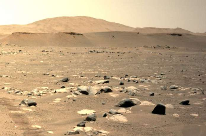 नासा की यह तस्वीर 25 अप्रैल, 2021 को अपनी तीसरी उड़ान के दौरान Ingenuity Mars Helicopter (C) को उड़ते हुए दिखाती है, जैसा कि बाएं N ने देखा है