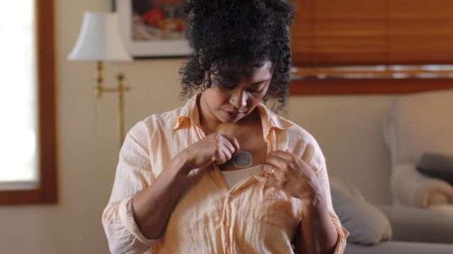 Cette image non datée avec l'aimable autorisation de BioIntelliSense, Inc., montre une femme plaçant le BioButton, l'un des appareils portables montrés dans fightin
