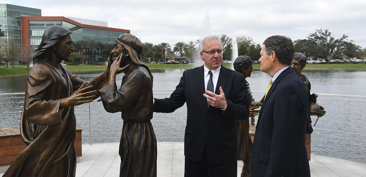 Sculptor Victor Issa (left) talks with Ted Hamilton, AdventHealth's chief mission integration officer, about The Master Healer statue on the campus of AdventHealth's corporate office in Altamonte Springs, Florida, United States. [Photo: Southern Tidings]