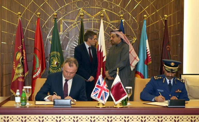 وزير الدفاع القطري خالد العطية ونظيره البريطاني غيفن ويليامسن يتبادلان الحديث خلال عملية توقيع الإتفاقية العسكرية بين البلدين في الدوحة (AFP)