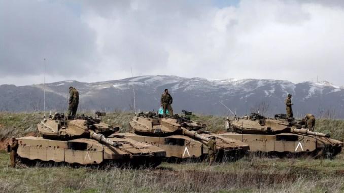 جنود إسرائيليون يقفون على دباباتهم المطلة على الحدود بين إسرائيل وسوريا. (رونين زفولون/ريوترز)