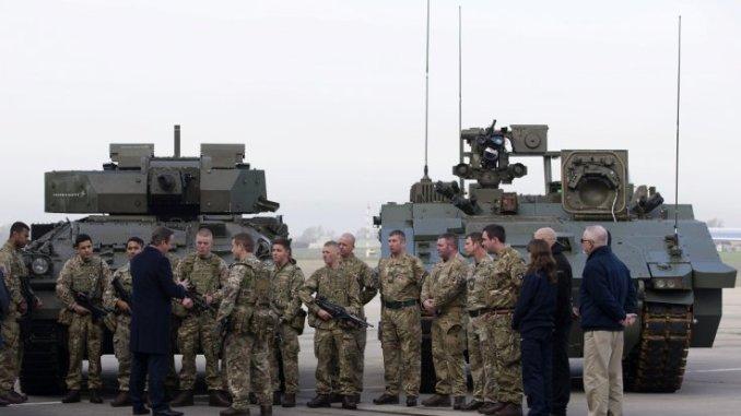 """رئيس الوزراء البريطاني ديفيد كاميرون يتحدّث مع جنود من المشاة الويلزية الملكية وهم يقفون أمام مركبة مشاة قتالية من إنتاج لوكهيد مارتن (إلى اليسار) ومركبة قتالية مدرعة من طراز """"أجاكس"""" من إنتاج جنرال داينامكس (إلى اليمين) في قاعدة نورثولت في لندن (رويترز)"""