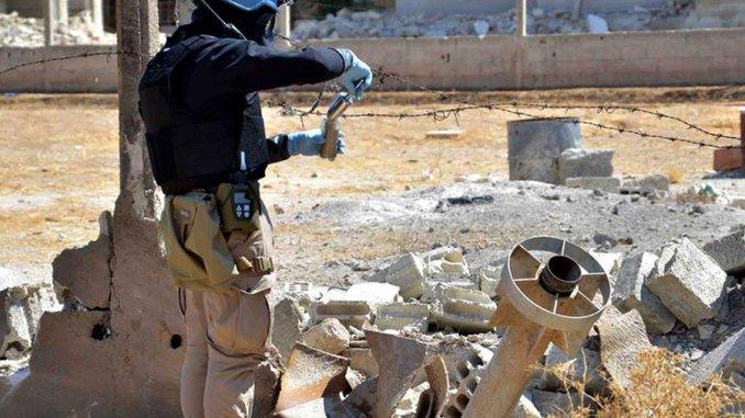 عضو من فريق التحقيق التابع للأمم المتحدة يقوم بجمع عينات من الرمال بالقرب من جزء من صاروخ استخدم في الهجمات الكيماوية المميتة على الغوطة في 28 آب/أغسطس 2013 (AP)