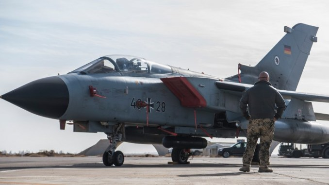طيار في سلاح الجو الألماني يقف أمام مقاتلة تورنادو في قاعدة الأزرق الجوية في الأردن في 13 كانون الثاني/يناير 2018، حيث قامت وزيرة الدفاع الألمانية أورسولا فون دير ليين بزيارة إلى الوحدة الألمانية هناك (AFP)