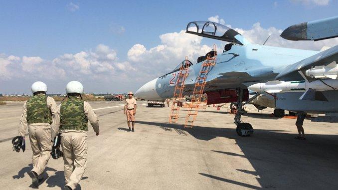 صورة التقطت في 5 تشرين الأول/أكتوبر 2015 تظهر طيارين وتقنيين روس أمام مقاتلة سوخوي-30 في قاعدة حميميم الجوية في محافظة اللاذقية السورية (AFP)