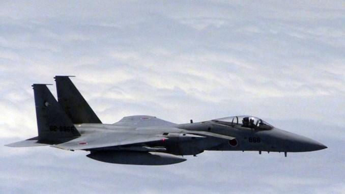 صورة التقطت في 11 حزيران/يونيو 2014، والتي نشرتها وزارة الدفاع الوطني لجمهورية الصين الشعبية، تُظهر طائرة يابانية من طراز أف-15 تقترب من طائرة صينية (خارج الإطار) في مكان تتداخل فيه مناطق الدفاع الجوي في البلدين (AFP)