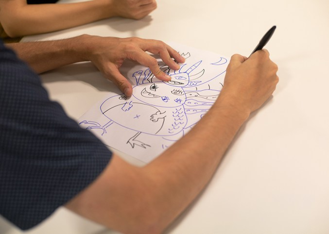 Man drawing a monster as part of the monster creator icebreaker.