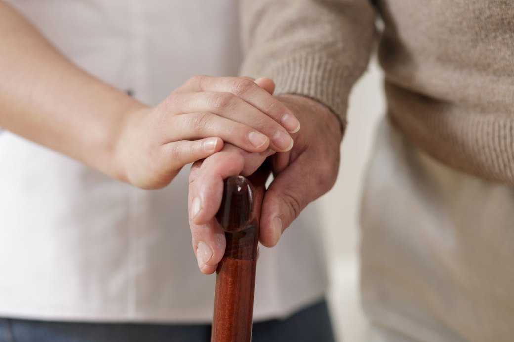 caregiver holding the hand of an elderly man with a cane