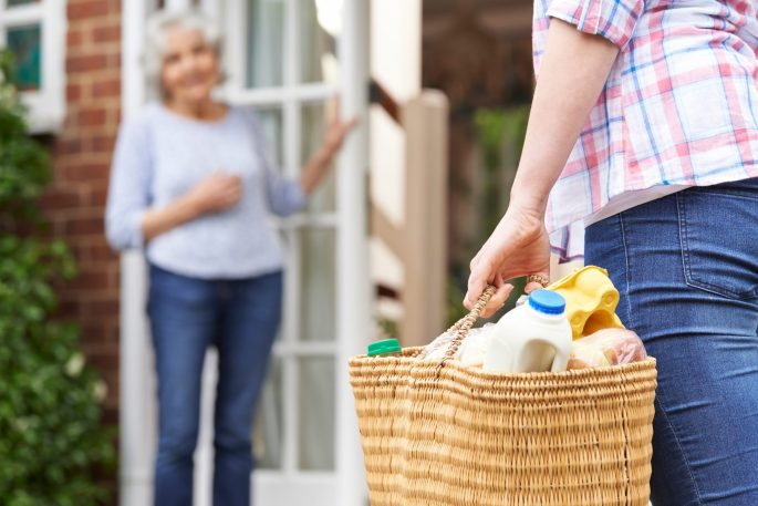 Woman delivering groceries to elderly neighbor