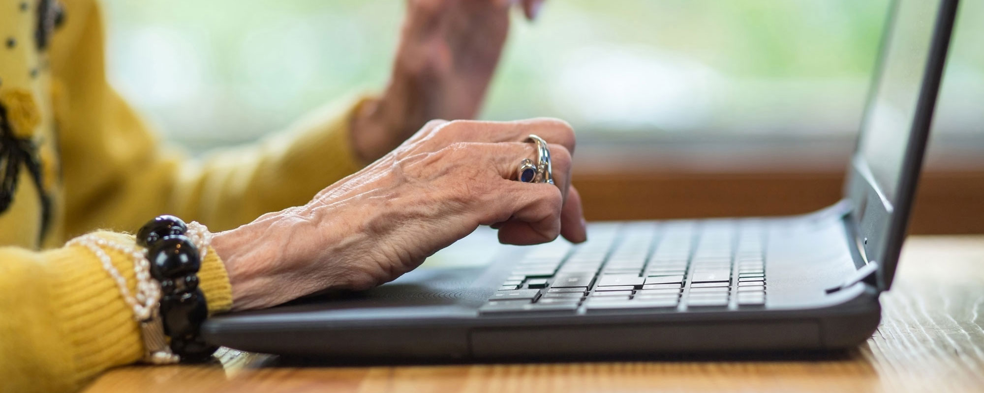close up of older woman's hands typing on a laptop computer