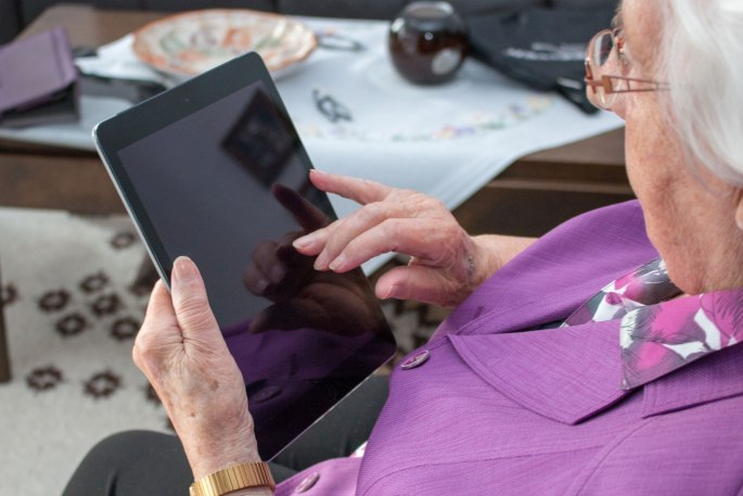 An older woman alone in her home communicates using a tablet