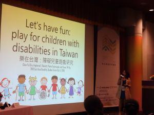邱春瑜站在大螢幕前發表,投影片上寫:樂在台灣:障礙兒童遊戲研究。下方有一排插畫為多元種族、能力,性別的小孩們牽著手,有的小孩拿拐杖和坐輪椅。