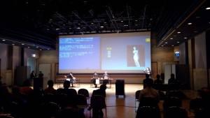 照片中分講者坐在投影片的大螢幕前演講的現場,可見講者身旁坐著日籍翻譯,旁邊也站了手語翻譯員。大螢幕投影片顯示一個缺了手臂的古典歐式雕塑品,一旁投影片是日文的即時字幕。照片可見黑壓壓的聽眾背影