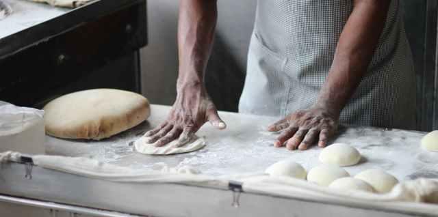 man preparing dough for bread