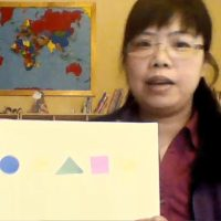 teacher shows paper with shapes