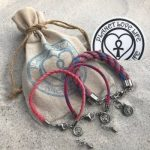 Three pink Planet Love Life bracelets lie on the sand next to a brown drag string bag with the company logo.
