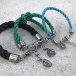 Three Planet Love Life bracelets in black, green and blue.
