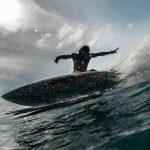 Shop: A man riding a wave on a surf board.