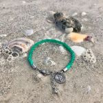 A Planet Love Life bracelet in green lies among shells on a sandy beach.