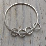 A solid silver bracelet with four smaller rings on the bangle.