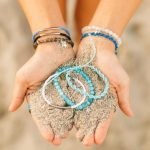 Shop: Two hands cupping sand with Devocean bracelets in green.