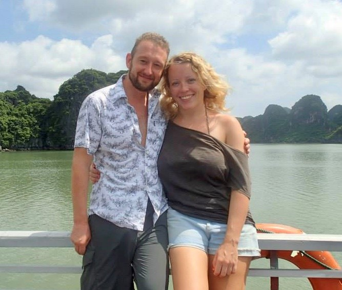 A picture of the Sea Fans' founders Jerry Slater and Amy Hornett standing on the side of a boat in Vietnam.