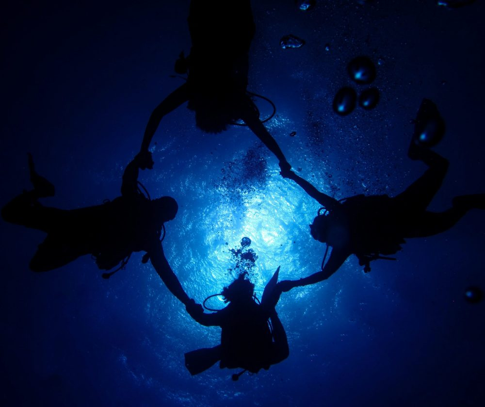 Four divemasters forming a circle underwater