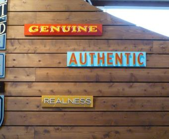 "Wall with signs saying ""Genuine"" and ""authentic"". Is authenticity part of your brands social media strategy"